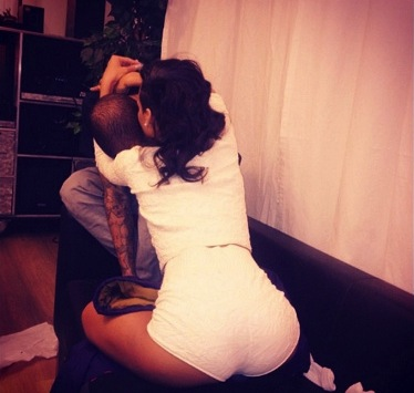 Rihanna sitting in Chris Brown's lap